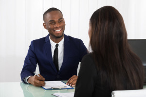 55430077 - male manager interviewing a young female applicant in office