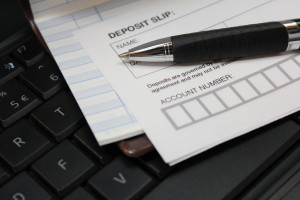 26813186 - deposit slip with pen and check book register on keyboard