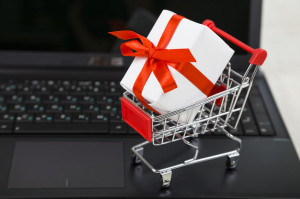 Shopping cart with gift box on laptop. Concept of shopping onlin